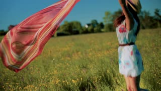 Happy girl playing with scarf on the meadow