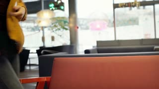 Happy girl sits down on the sofa in the stylish cafe and texting on smartphone