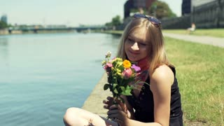 Happy girl sitting by the river and holding colorful bunch of flowers