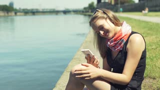 Happy girl sitting by the river and recall memories by looking on the photos