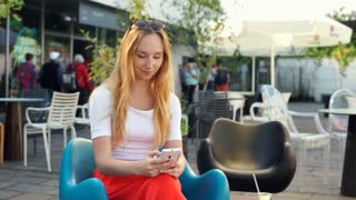 Happy girl sitting in the stylish, outdoor cafe and using smartphone