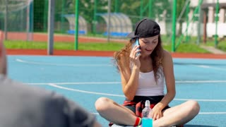 Happy girl sitting on sports field and chatting on cellphone