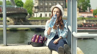 Happy girl sitting on the bridge and drinking water from the bottle