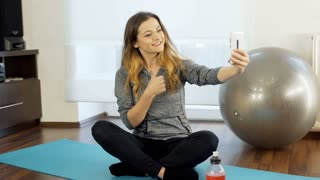 Happy girl sitting on the exercising mat and doing selfies on smartphone, steady