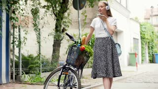 Happy girl standing with her bicycle and talking on cellphone