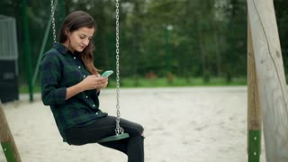 Happy girl swinging on the seesaw and using smartphone, steadycam shot
