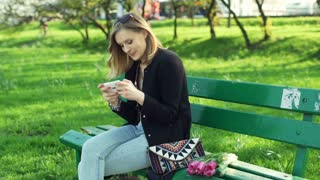 Happy girl texting on smartphone while sitting on the bench in park