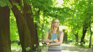 Happy girl walking on path in the park and holding books