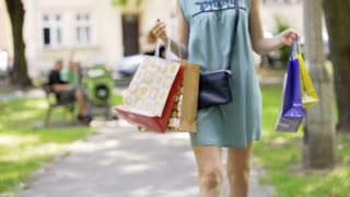 Happy girl walking with shopping bags in the park and looking on her purchase