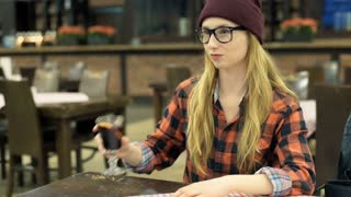 Happy, hipster girl drinking beverage and doing selfies in the cafe, steadycam s