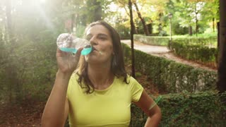Happy jogger drinking energy drink after run, steadycam shot