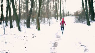 Happy jogger running toward camera at winter time, steady, slow motion shot