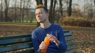 Happy man drinking orange juice and relaxing in the park, steadycam shot