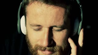 Happy man having his eyes closed and listening music on headphones