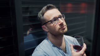 Happy man leaning on window and drinking red wine