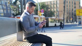 Happy man playing on smartphone and sitting on street bench.