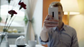 Happy man sitting in the cafe and doing selfies on smartphone