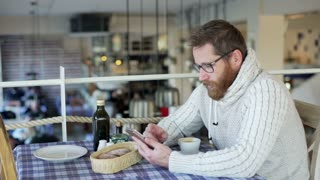 Happy man sitting in the restaurant and browsing internet on smartphone