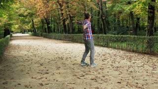 Happy man spinning around in the park, steadycam shot