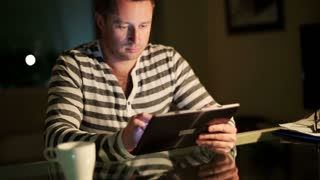 Happy man using tablet at night by the table.