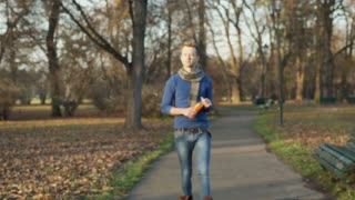 Happy man walking in the autumnal park and holding orange juice, steadycam shot