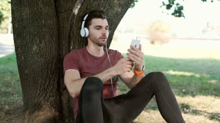 Happy man wearing headphones and having a videocall on smartphone