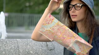 Happy tourist holding map and waving to someone, steadycam shot, slow motion sho