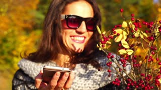 Happy woman holding cellphone and bouquet of brier, steadycam shot, slow motion