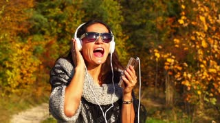 Happy woman listening music on headphones, steadycam shot, slow motion shot