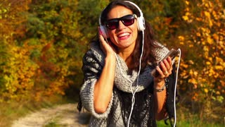Happy woman listening music on headphones, steadycam, slow motion shot at 240fps