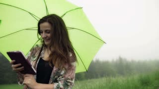 Happy woman looking on tablet and holding umbrella