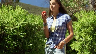 Happy woman looking to the camera and eating apple while standing in the bushes