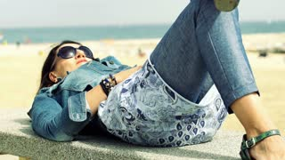 Happy woman lying on the stone next to the beach, steadycam shot