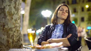 Happy woman relaxing in the city at night, steadycam shot