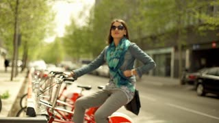 Happy woman sitting on the bicycle in the city, steadycam shot