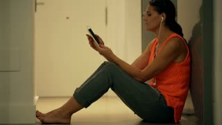 Happy woman sitting on the floor and listening music on smartphone