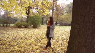 Happy woman standing in the park, steadycam shot, slow motion shot
