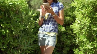Happy woman standing next to the bushes and browsing internet on smartphone