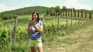 Happy woman standing next to the vineyard and doing selfies on smartphone, stead