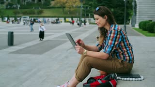 Happy woman using tablet in public square, steadycam shot
