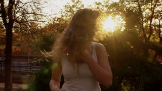 Happy woman waving hairs in the park, steadycam shot