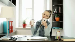 Happy woman with ponytail browsing internet on smartphone and drinking coffee, s