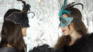 Happy women chatting with each other at the masquerade party, steadycam shot
