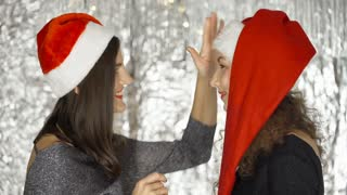 Happy women wearing Santa's hats and chatting with each other, steadycam shot