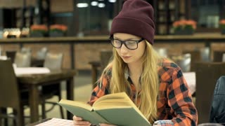 Hipster girl receives message on smartphone while reading book, steadycam shot