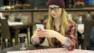 Hipster girl using smartphone and smiling to the camera in the cafe, steadycam s