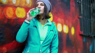 Hipster woman drinking water from a bottle, steadycam shot, slow motion shot