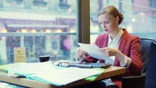 Irritated businesswoman finish checking papers and looking on smartphone