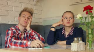 Irritated couple sitting in the cafe and waiting for their order