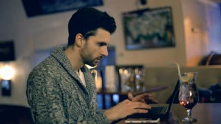 Irritated man having a problem while using laptop in the restaurant